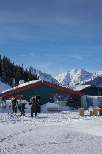 Ski patrol leaving Cloud Nine Alpine Bistro with Maroon Bells in the background