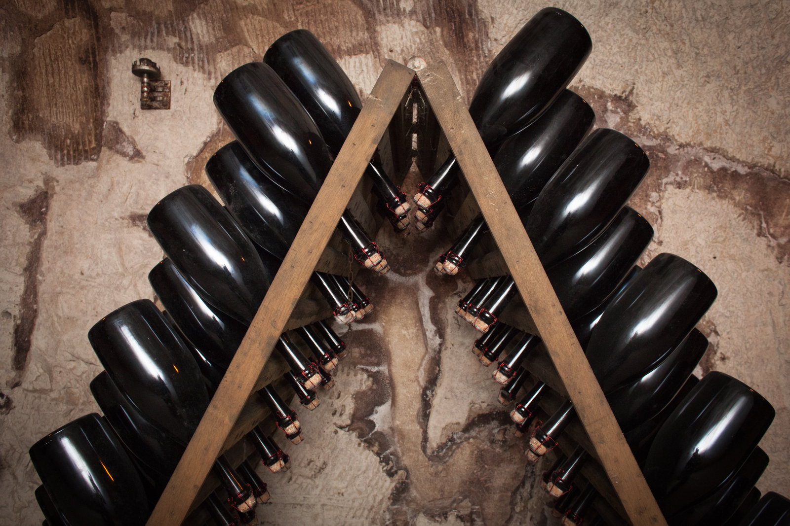 Bottles of Champagne in riddling racks in the underground cellars at Champagne Gosset. ©Kevin Day / Opening a Bottle
