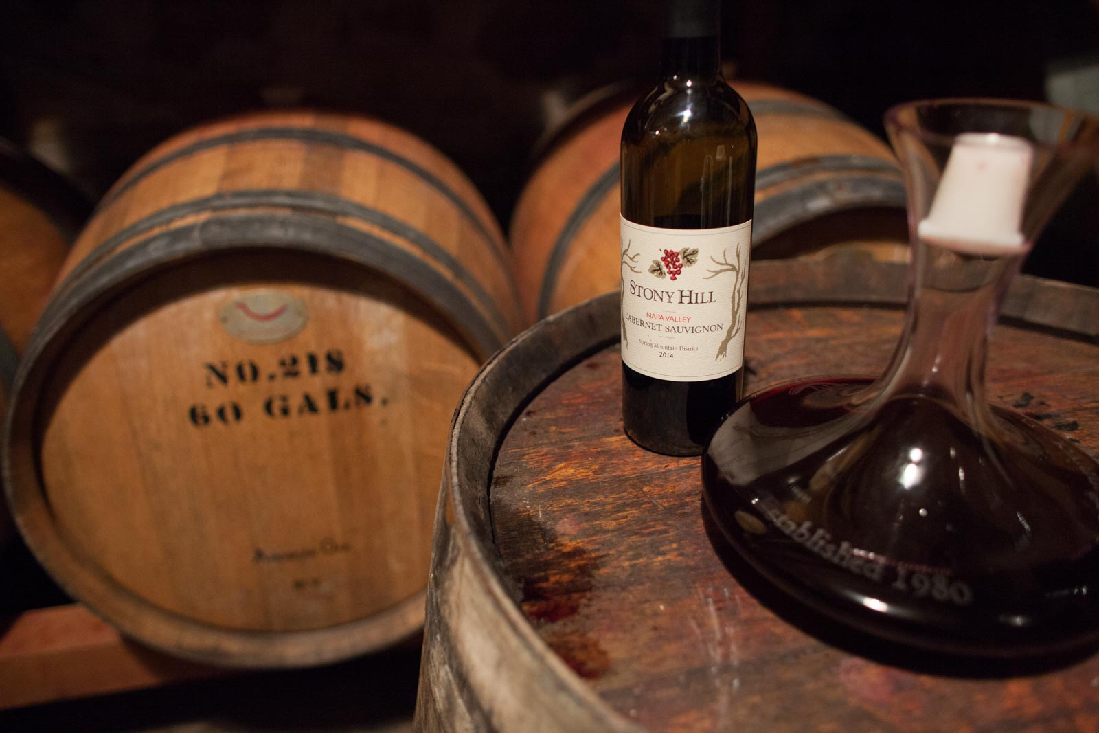 Amongst the barrels at Stony Hill Vineyards, with a bottle of 2014 Cabernet Sauvignon while the 2016 vintage ages beside it. ©Kevin Day / Opening a Bottle
