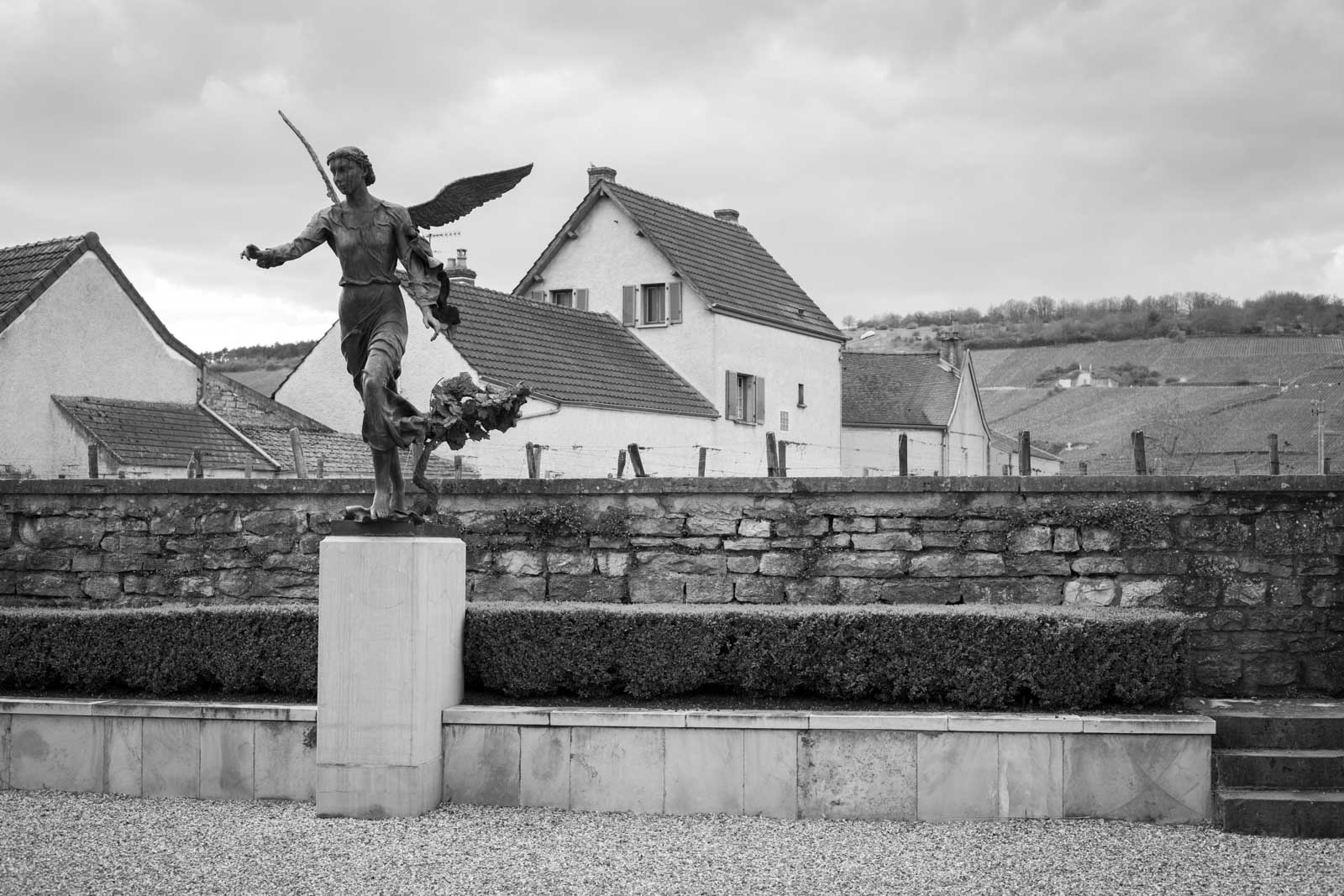 The angel-crowned courtyard at Domaine de la Romanée-Conti, in the village of Vosne-Romanée. The Grand Cru vineyard of Romanée-St-Vivant is just beyond the stone wall. ©Kevin Day / Opening a Bottle