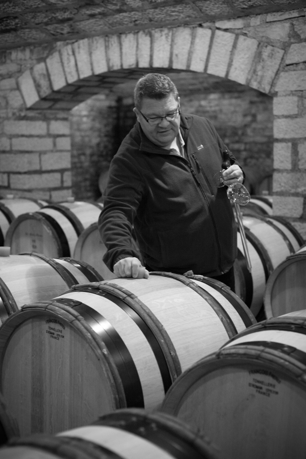 Bertrand de Villaine in the cellar of Domaine de la Romanée-Conti. Notice the stones he has placed on the edge of the barrel; his way of indicating which barrel has been sampled so he can return the wine when the tasting is done. One of many little touches that makes the experience at Domaine de la Romanée-Conti so unique. ©Kevin Day / Opening a Bottle