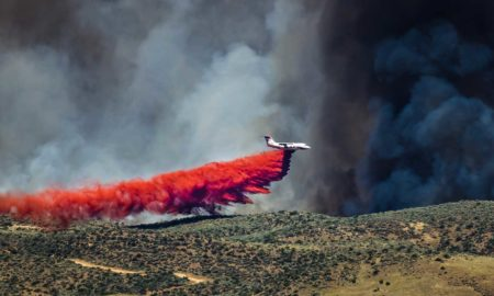 A plane drops fire retardant on a wildfire.