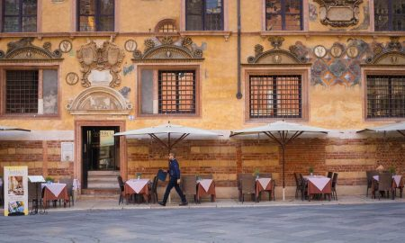 A waiter walks by a caffé in Piazza dei Signori, Verona.