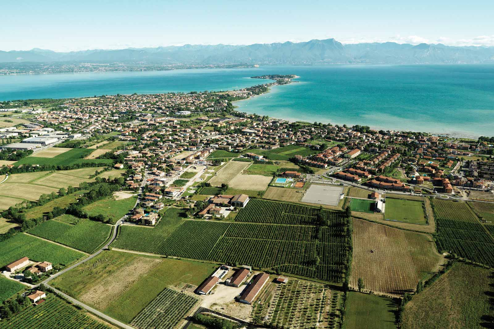 An aerial view of Lugana DOC reveals its proximity to Lake Garda and the Alps in the distance. ©Consorzio Tutela Lugana DOC