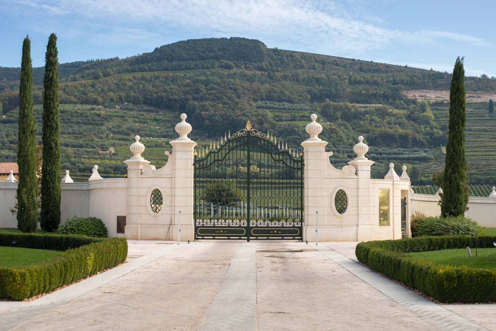 The entrance gate to the winery with vineyards on the hillside in the distance. ©Kevin Day/Opening a Bottle