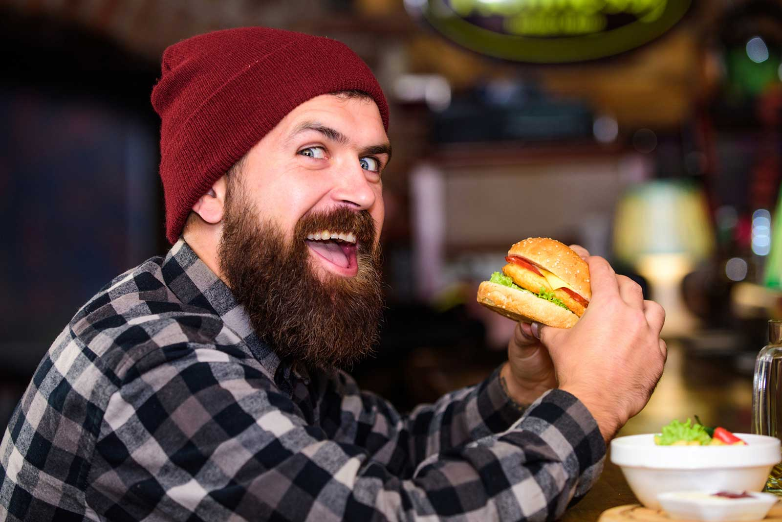 "I couldn't write a better caption than the one provided by BigStockPhoto: ""Hipster hungry man eat burger. Man with beard eat burger menu. Brutal hipster bearded man sit at bar counter. High calorie food. Cheat meal. Delicious burger concept. Enjoy taste of fresh burger"""