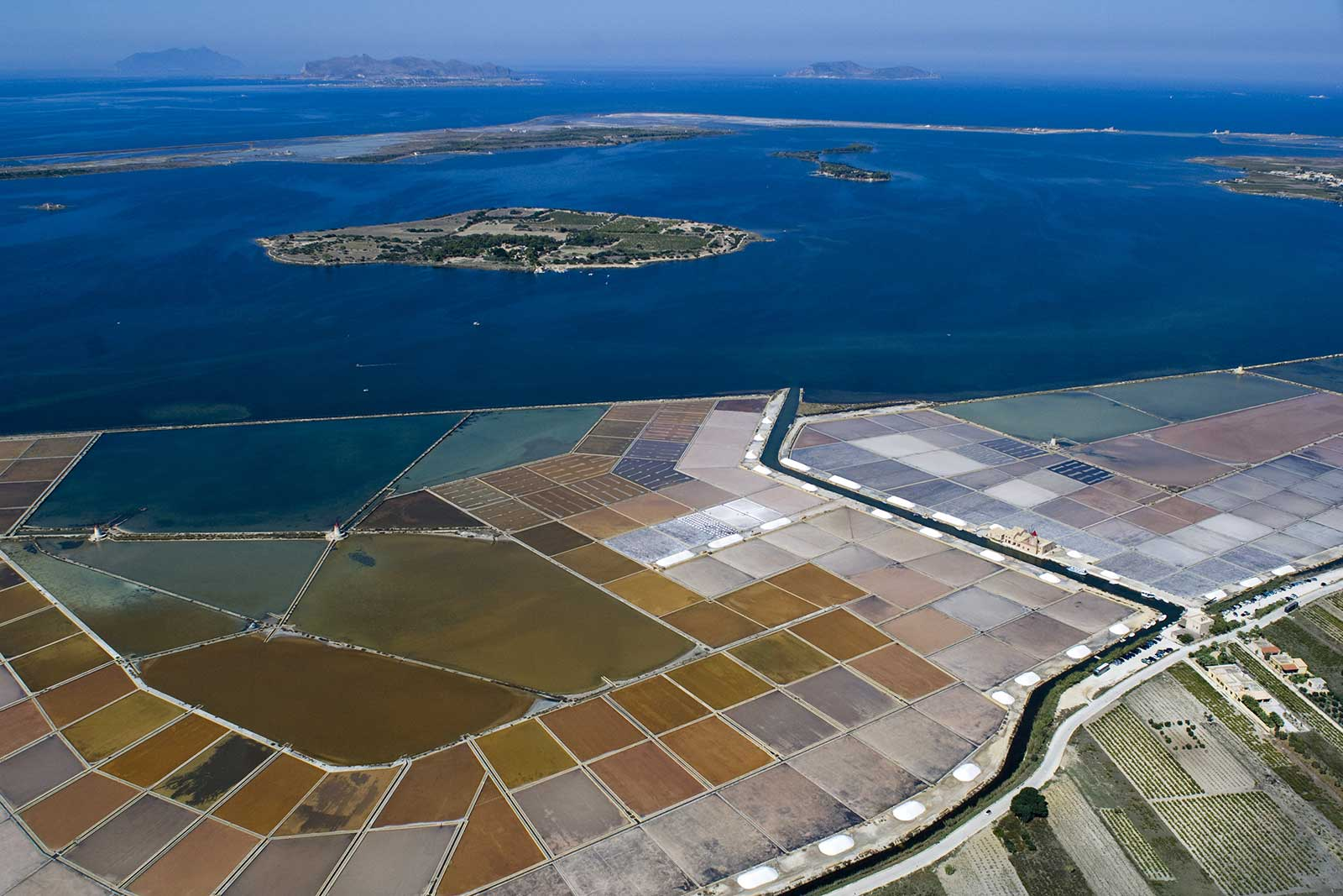 The island of Mozia is seen in the middle of the lagoon, with the famous salt pans running along the shore. Stock photo.